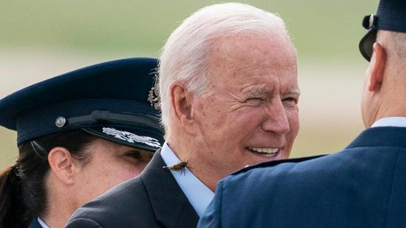 President Joe Biden, with a brood X cicada on his back, walks to board Air Force One upon departure, Wednesday, June 9, 2021, at Andrews Air Force Base, Md. Biden is embarking on the first overseas trip of his term.
