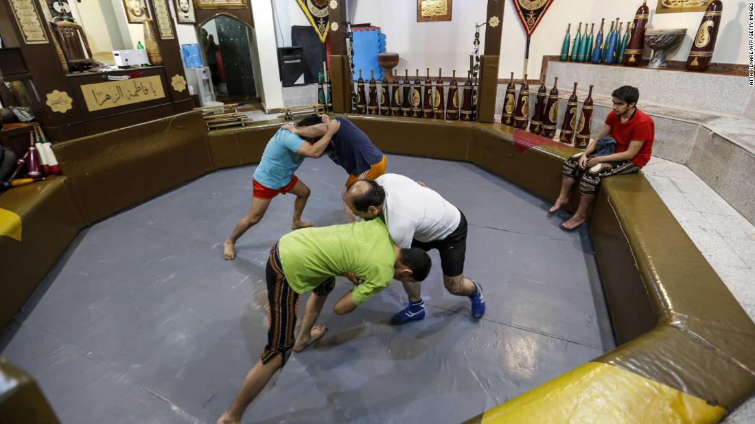 """Iranians wrestle during a workout session at the traditional Shir Afkan """"zurkhaneh"""" (House of Strength) gymnasium in the capital Tehran in February 2018."""