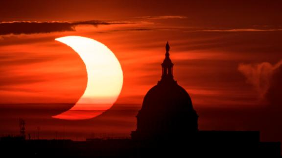 """ARLINGTON, VIRGINIA - JUNE 10: In this handout image provided by NASA, a partial solar eclipse is seen as the sun rises behind the Capitol Building on June 10, 2021 in Arlington, Virginia. Northeast states in the U.S. will see a rare eclipsed sunrise, while in other parts of the Northern Hemisphere, this annular eclipse will be seen as a visible thin outer ring of the sun's disk that is not completely covered by the smaller dark disk of the moon, a so-called """"ring of fire"""". (Photo by Bill Ingalls/NASA via Getty Images)"""