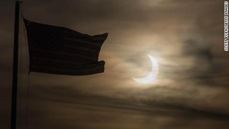 An eclipsed sun rises next to a flag on June 10 in Scituate, Massachusetts.