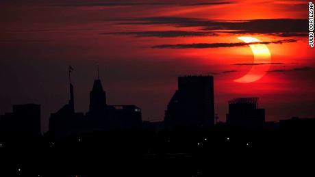 A partial solar eclipse rises over the Baltimore skyline, Thursday, June 10.