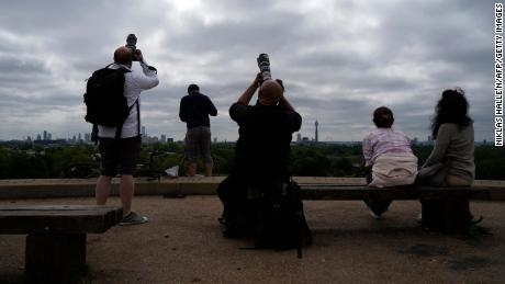 People photograph a partial solar eclipse through cloud cover from Primrose Hill in central London on June 10.