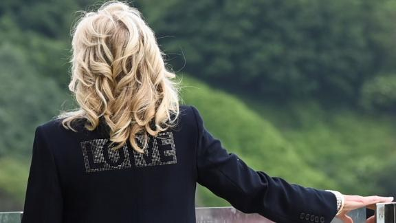 """ST IVES, ENGLAND - JUNE 10:  First Lady Jill Biden, wearing a jacket with the phrase """"Love"""" on the back, stands outside the Carbis Bay Hotel on June 10, 2021 in St Ives, England. UK Prime Minister, Boris Johnson, will host leaders from the USA, Japan, Germany, France, Italy and Canada at the G7 Summit which begins on Friday, June 11 2021. (Photo by Toby Melville-WPA Pool/Getty Images)"""
