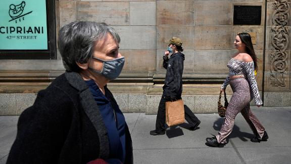 People are seen walking along 42nd Street, some with masks and others without, as The Centers for Disease Control and Prevention eased its guidelines on wearing masks outdoors, saying only fully vaccinated people do not need to cover their faces unless in a large crowd, New York, NY, April 27, 2021. A growing number of people who have received their first dose of vaccine are not going back for their second shot, reducing the efficacy of the vaccine and compromising their immunity to COVID-19. (Photo by Anthony Behar/Sipa USA)(Sipa via AP Images)