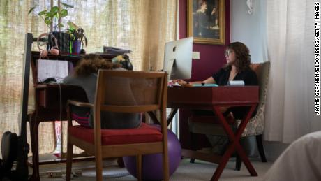 A mother teleworks while her daughter virtually attends school at their home in Miami Beach on September 8, 2020.