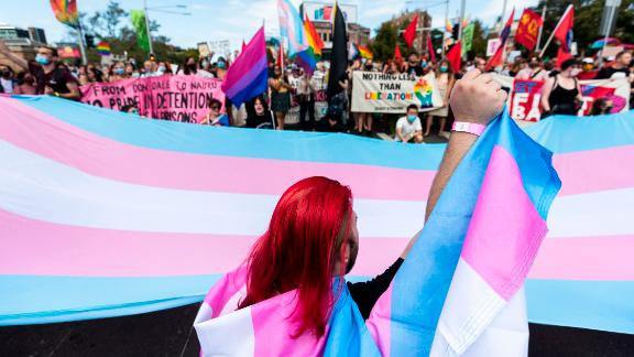 Protesters gather ahead of the Sydney Gay and Lesbian Mardi Gras parade next to a banner with the colors of the trans movement on March 6 in Australia.