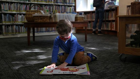 Libraries are slowly re-opening. Two-year-old Frank visited the Oakland Public Library's Rockridge Branch with his father.