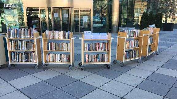 Racks of books are seen during the pandemic in front of the Hartford Public Library, where librarians have had to reimagine the services they offer.