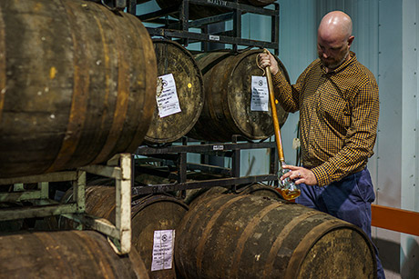 Town Branch Distillery Blender and Distiller Alan Kennedy uses a whiskey thief to extract bourbon from a freshly tapped barrel.