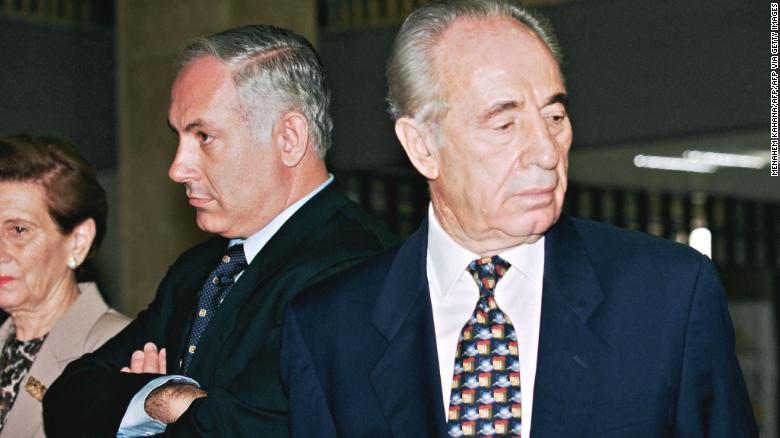 Netanyahu, yang saat itu menjadi perdana menteri terpilih Israel, berdiri di samping Perdana Menteri Shimon Peres di Knesset pada tahun 1996