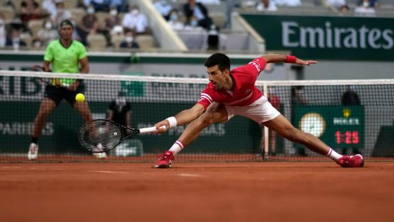 Novak Djokovic stretches to return the ball during his French Open semifinal match against Rafa Nadal.
