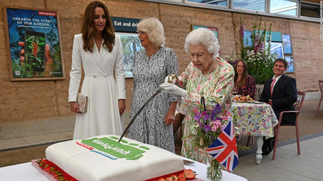 Queen shows off sword skills by cutting cake during G7