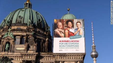 A vaccine campaign poster hangs at Berlin Cathedral in March. The government is facing some heat for its absurd approach on the public awareness campaigns.