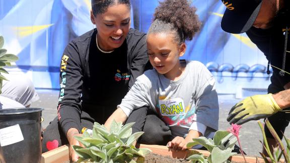 Ayesha Curry and daughter Ryan add plants to the garden area.