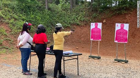 Three women attend a shooting event put on by the National African American Gun Association at a range in Covington, Georgia, on Sunday, June 13, 2021.