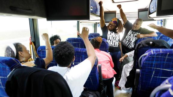 In this August 2018 photo, Black Voters Matter Fund co-founders LaTosha Brown, left, and Cliff Albright, right, lead Mississippi grassroots partners in some empowerment cheers aboard a bus tour to Greenville, Mississippi.