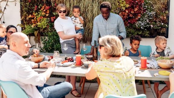 family, friends, adults, and kids having fun sitting or standing around the table on a sunny summer day.
