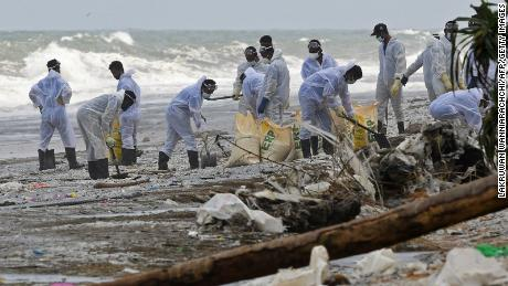 Members of the Sri Lanka Navy remove debris washed ashore from the burning container ship, in the sea off Colombo harbor on May 31.