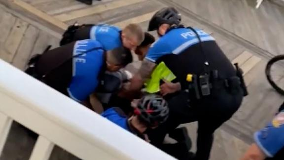 """Two different videos showing several arrests made by Ocean City Police in Maryland following their enforcement of smoking ordinance violations on Saturday have gone viral, with viewers questioning the use-of-force techniques applied by officers responding to the incidents. CNN has not seen video of what happened at the beginning of this incident. In videos obtained by CNN and confirmed by Ocean City Police to show parts of the incident, police are seen arresting at least three individuals as a crowd of people gathers around. In one video, one of the people being arrested is held down by five officers as one officer can be heard saying something about resisting. """"I'm not resisting,"""" the teenager answers, face down on the boardwalk. As the teen asks officers why he's being arrested, one of the officers begins to knee the individual in the side, while two of the other officers pull away. The officer eventually knees the man five times before officers appear to put the man in handcuffs."""
