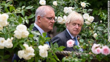 Britain's Prime Minister Boris Johnson (R) and Australia's Prime Minister Scott Morrison walk in the garden of 10 Downing street in central London on June 15, 2021.