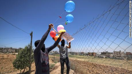 Masked Palestinian supporters of the Islamic Jihad movement prepare incendiary balloons on Tuesday.
