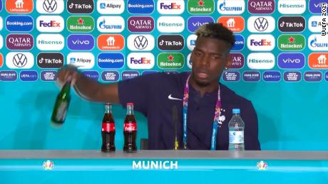 Pogba, who starred in France's 1-0 victory against Germany, removes a Heineken bottle during a press conference.