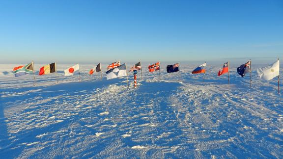 The True South flag flies alongside  the flags of the original 12 Antarctic Treaty Signatories at the ceremonial South Pole.