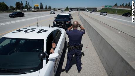 California Highway Patrol officer Matthew Musselmann uses a laser gun to detect speeders on Interstate 5 on April 23, 2020, in Anaheim.