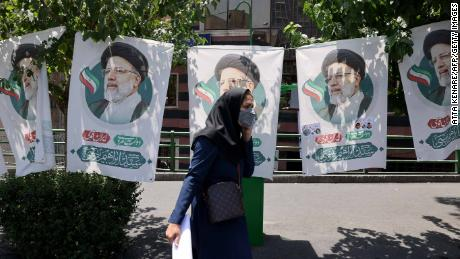 An Iranian woman walks past banners of ultraconservative cleric and presidential candidate Ebrahim Raisi, in Tehran, on June 17, 2021.