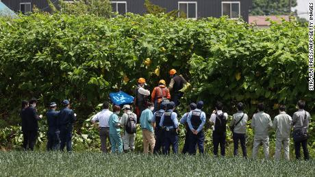Police officers and members of a hunting group search for a brown bear on the loose in Sapporo, Japan, on June 18.