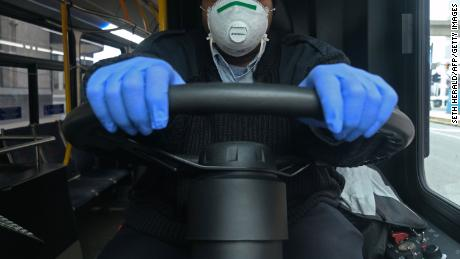 A bus driver for the Detroit city bus line DDOT poses for a portrait wearing a protective mask and gloves for protection in Detroit on March 24, 2020, during the novel coronavirus outbreak.