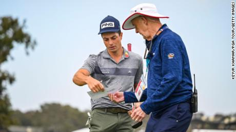 Hovland (left) reviews his scorecard  during the second round of the US Open at Torrey Pines, California.