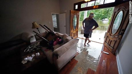 Danny Gonzales walks in his flooded house Saturday after Claudette passed through Slidell, Lousiana.