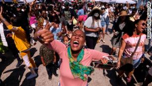 People dance as they celebrate during a Juneteenth commemoration at Leimert Park Plaza on Saturday, June 19, 2021, in Los Angeles.