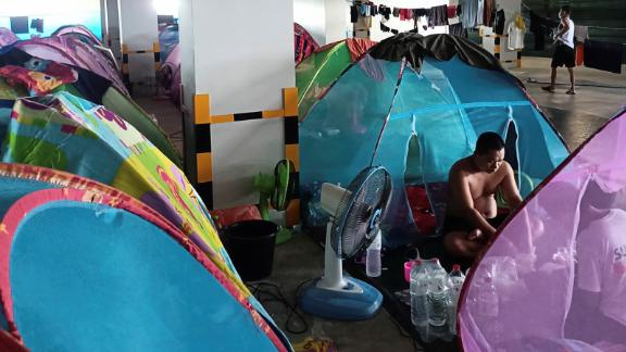 Migrant workers from Myanmar pass their time near their mosquito net tents at Cal-Comp Electronics factory while under quarantine, Phetchaburi, Thailand June 8, 2021. Picture taken June 8, 2021. REUTERS/Stringer NO RESALES. NO ARCHIVE.