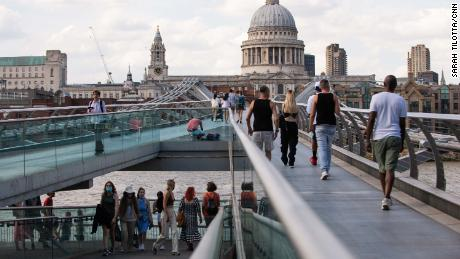 Pedestrians, some in masks, cross London's Millennium footbridge. The British government didn't make face coverings compulsory indoors or on public transport until last summer, and masks have never been mandated outdoors.