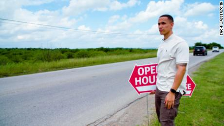 Sebastian Battle puts up signs for an open house he's hosting in the Austin-suburb of Manor, Texas.