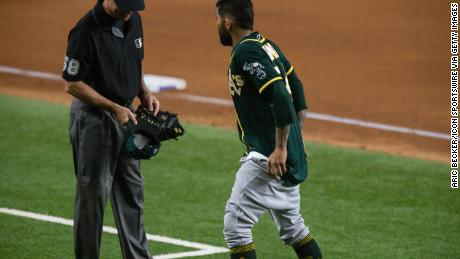 Oakland Athletics pitcher Sergio Romo gives umpire Dan Iassogna his hat and glove and pulls down his pants during a game Tuesday at Globe Life Field in Arlington, Texas.