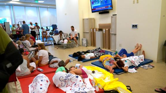 People lie on cots at the family reunification center in Surfside.
