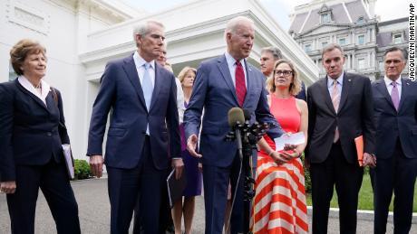 President Joe Biden, with a bipartisan group of senators, speaks outside the White House.