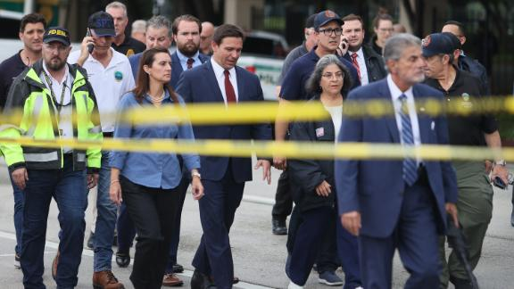 """Florida Gov. Ron DeSantis, at center in the red tie, arrives to speak to the media on June 24. """"We still have hope to be able to identify additional survivors,"""" DeSantis told reporters near the scene. """"The state of Florida, we're offering any assistance that we can."""""""