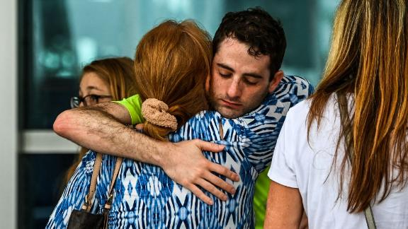 People hug at a family reunification center where evacuees were staying in Surfside.