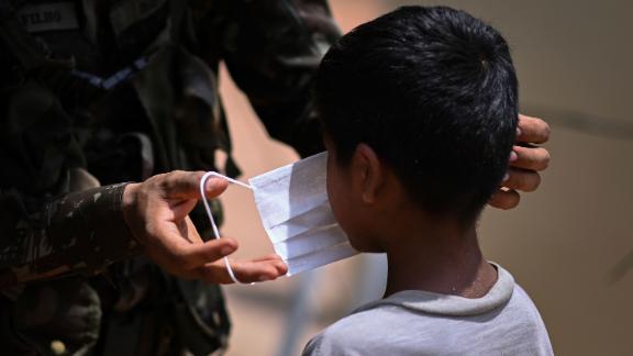 A member of the Brazilian Armed Forces puts a face mask in a child in the village of Urucu Jurua, Grajau, Maranhao state, Brazil, in October 2020.