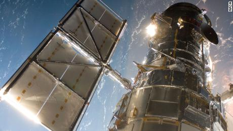 The space shuttle Atlantis captures the Hubble Space Telescope with its robotic arm. The moment marked the start of the mission to upgrade and repair the telescope, May 13, 2009.  - 210624161359 02 hubble space telescope scn large 169 - NASA's Space Shuttle Program: 8 pivotal moments