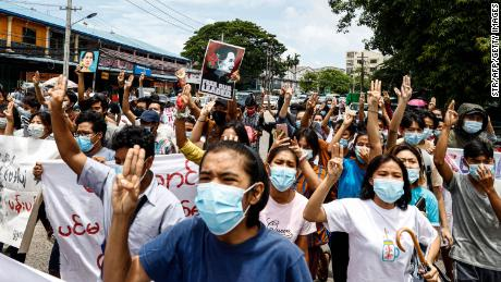 Protesters make the three-finger salute and hold posters of Myanmar's detained civilian leader Aung San Suu Kyi to mark her birthday as they take part in a demonstration against the military coup in Yangon on June 19, 2021.
