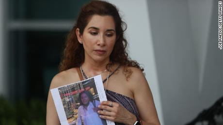 Luz Marina holds a picture of her aunt, Marina Azen, who she said is missing after the collapse.