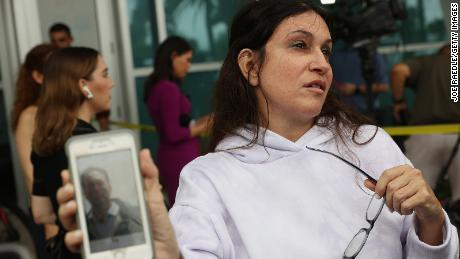 Soriya Cohen shows a picture of her husband, Brad Cohen, who she said is missing in the collapse.