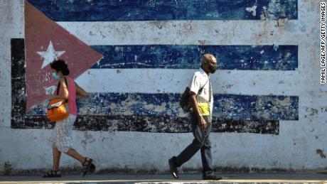 People walk near a mural depicting a Cuban flag in Havana, on April 16, 2021.