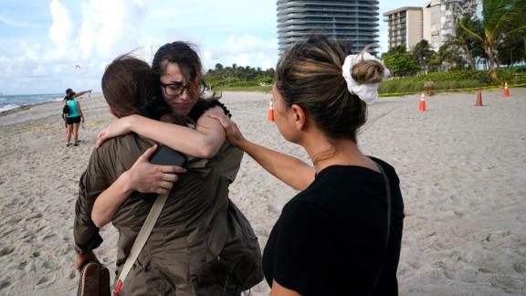 """Faydah Bushnaq, center, is hugged by Maria Fernanda Martinez as they stand on the beach near the building. Bushnaq, who was vacationing in South Florida, stopped to write """"pray for their souls"""" in the sand."""