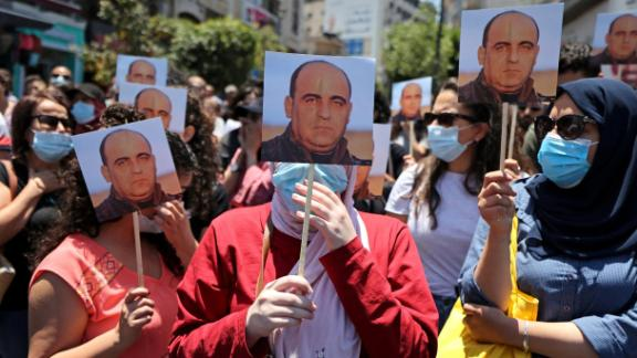 Protestors hold images of Palestinian activist Nizar Banat, who died while in the custody of PA security forces on Thursday morning.